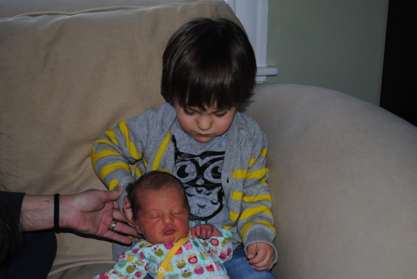 "Guess WHO ""held"" his sister for the first time? (Yes, they're both in owl gear)."