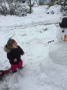 She finds this snowman very funny. Let's see how she feels about all the snow tomorrow.